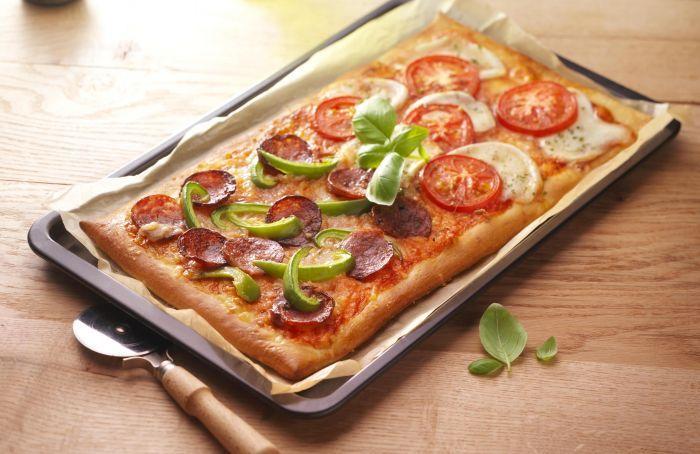 zelfgemaakte pizza met salami en tomaat